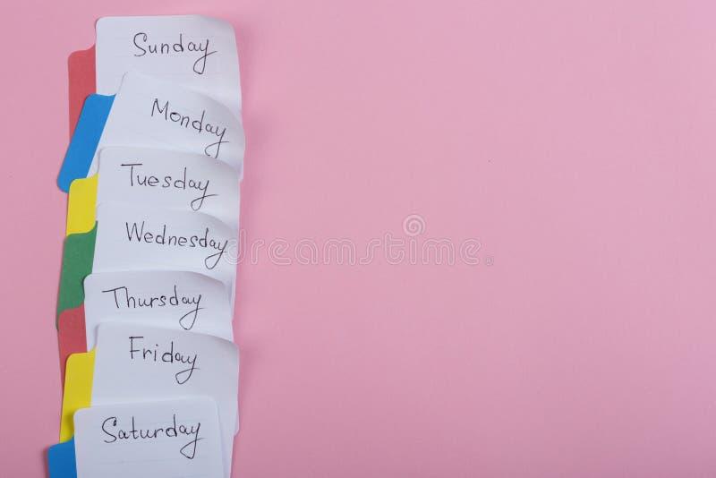 星期-纸贴纸附有桃红色背景 免版税图库摄影