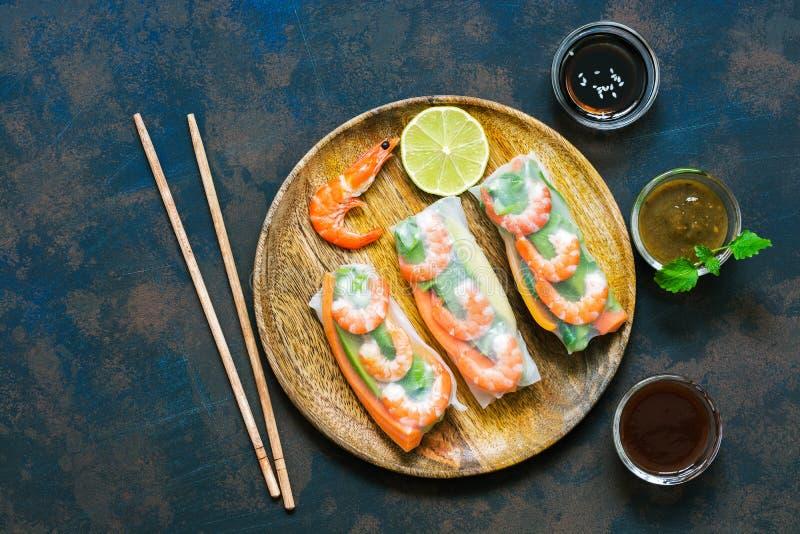 春卷用在宣纸的虾用各种各样的调味汁 土气蓝色生锈的背景 顶视图,拷贝空间 库存照片