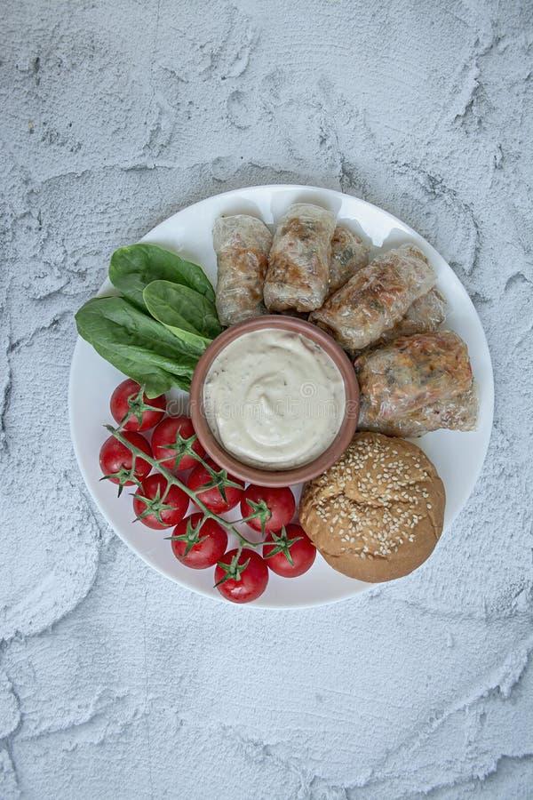 春卷用肉和菜在一个白色盘服务用调味汁 r 图库摄影