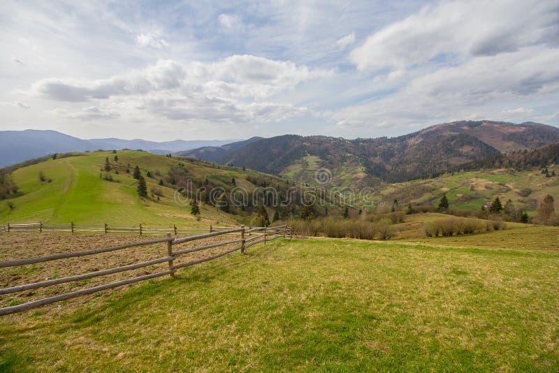 春天与木篱芭的村庄风景在前景 库存图片
