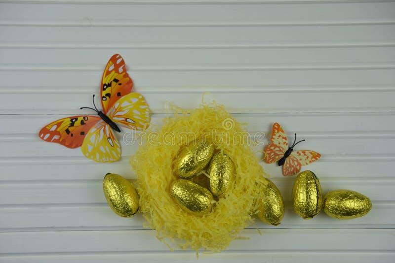 春天与黄色巢的复活节装饰用发光的金黄颜色鸡蛋和蝴蝶形状装饰填装了 图库摄影