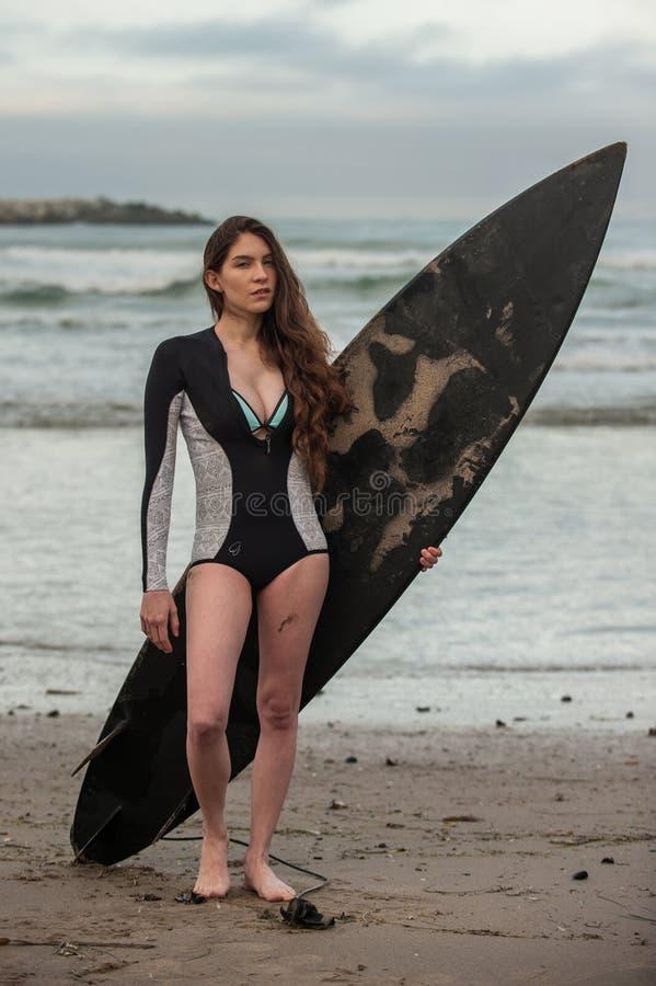 春天保温潜水服的女性冲浪者 库存照片