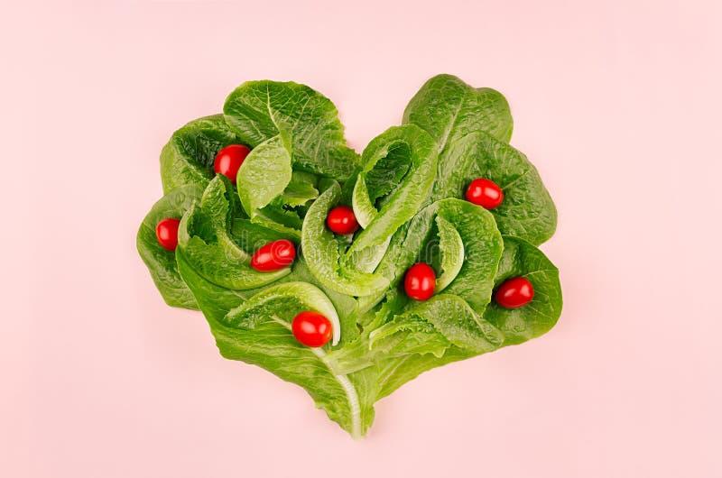 春天健康食物的心脏-在桃红色背景的西红柿和叶子菠菜 华伦泰` s天背景 库存照片