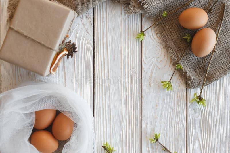 春天和复活节艺术 鸡蛋、分支用绿色新芽和一个礼物盒在白色木背景 免版税图库摄影