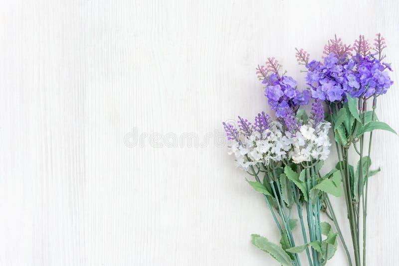 春天和晴天新鲜的淡紫色花在白色木桌背景 免版税库存图片