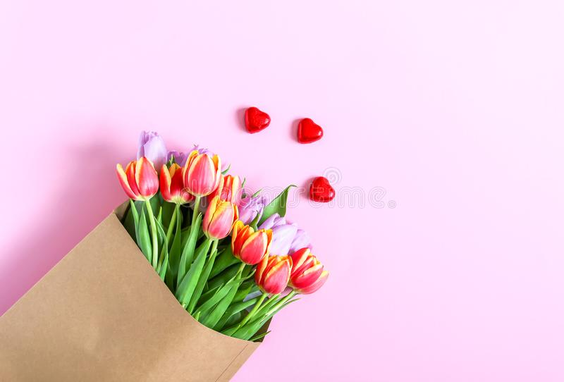 春天在工艺在软的桃红色背景的纸袋包裹的郁金香花花束  免版税图库摄影