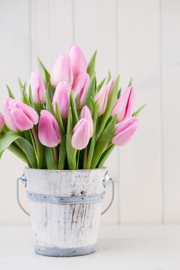 春天在桶的复活节郁金香在白色葡萄酒背景 库存照片