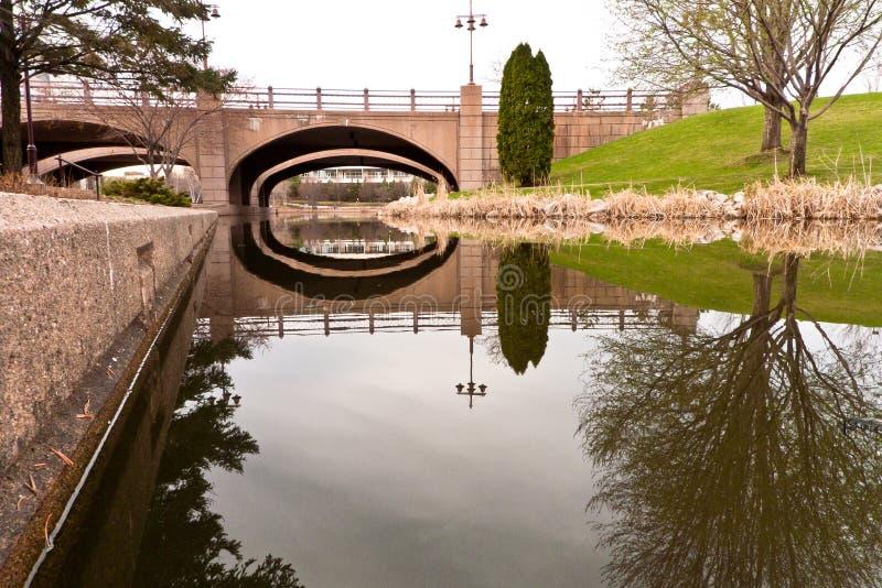 春天在百年湖公园 反射在水中的树和桥梁 库存图片