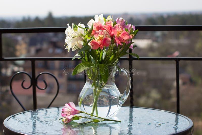 春天在玻璃水罐的花花束在桌上 免版税库存照片