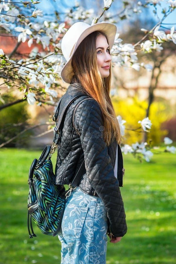 春天城市庭院佩带的外套和袋子的美丽的时尚行家妇女 免版税图库摄影
