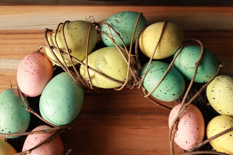 春天复活节花圈用在浅褐色的背景的五颜六色的鸡蛋 免版税库存照片