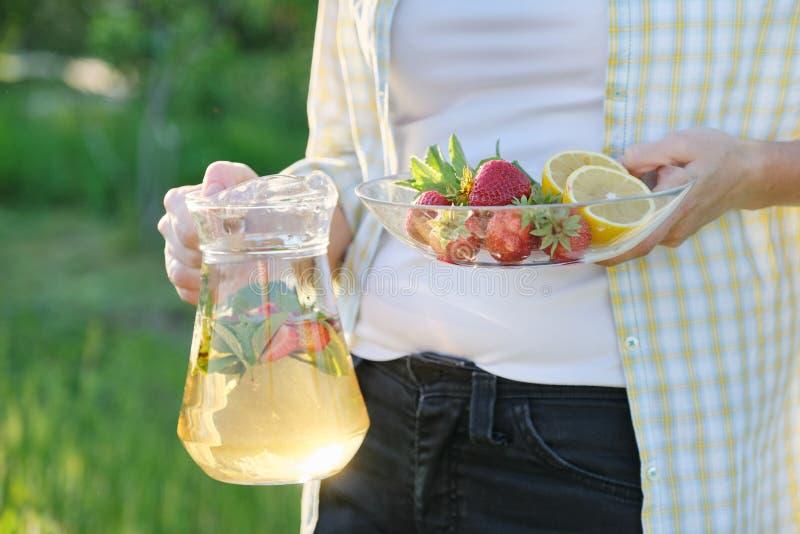 春天夏天茶点、妇女自然藏品瓶子的草莓薄菏和柠檬 库存图片