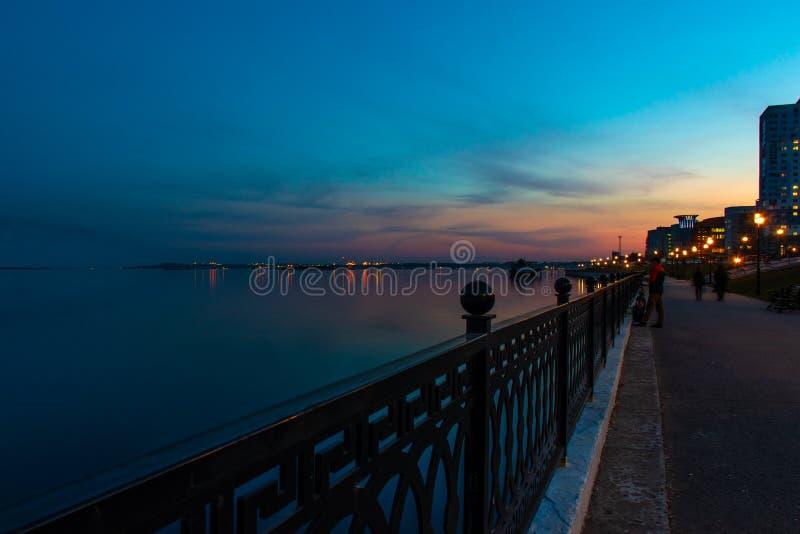 春天夜城市在日落下的萨拉托夫码头 街道装饰光和美丽的天空 免版税库存照片