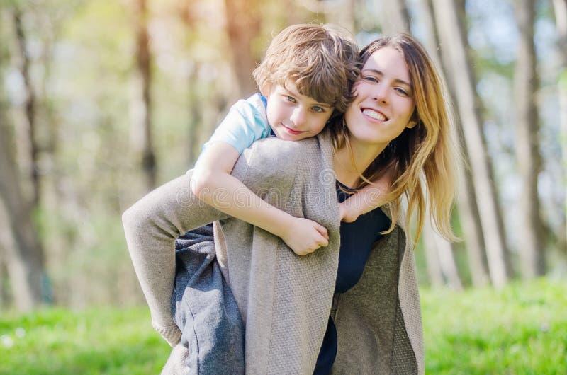 春天嬉戏的男孩拥抱母亲 免版税库存照片