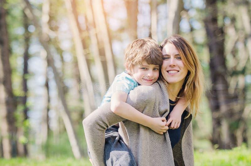 春天嬉戏的男孩拥抱母亲 免版税库存图片