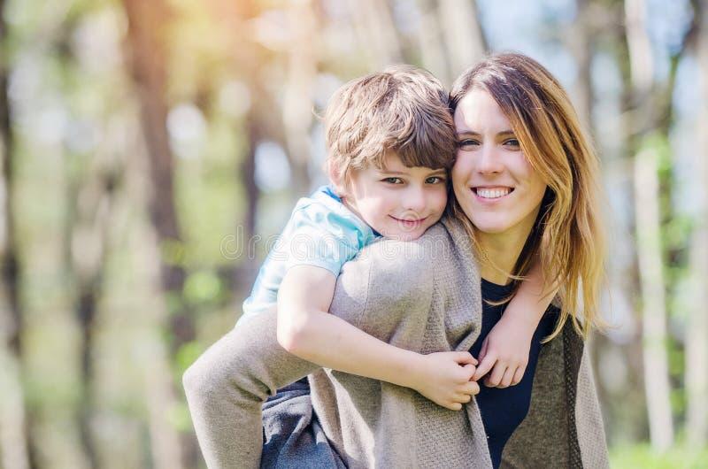 春天嬉戏的男孩拥抱母亲 免版税图库摄影