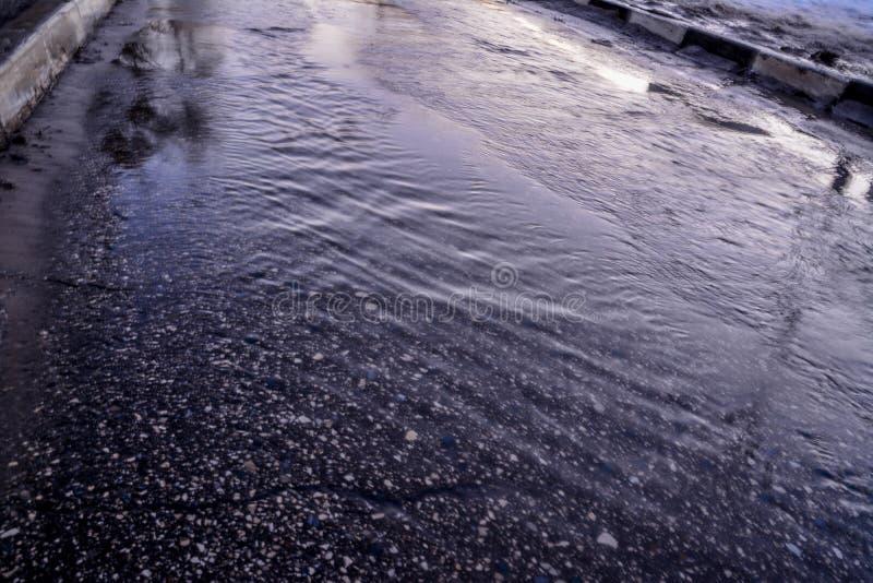 春天小河流经柏油路 库存图片