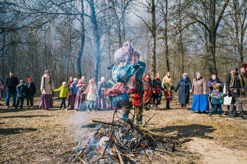 春天异教的节日  人们在圈子跳舞在烧被充塞的Maslenitsa附近在春天森林里 免版税库存照片