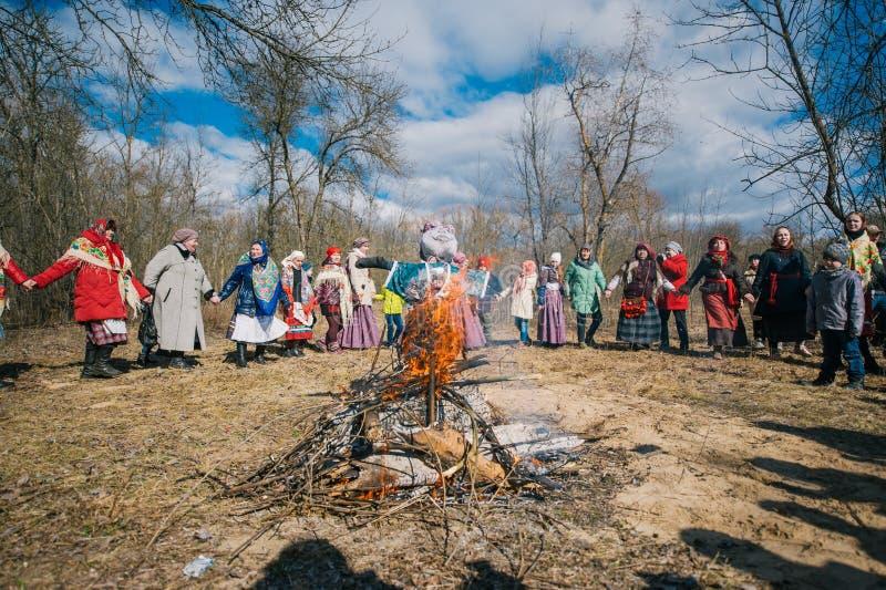 春天异教的节日  人们在圈子跳舞在烧被充塞的Maslenitsa附近在春天森林里 免版税图库摄影