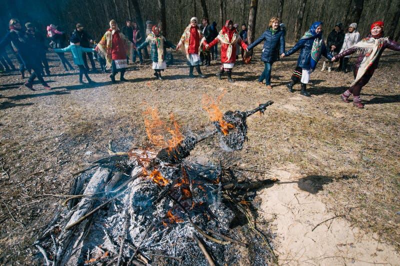 春天异教的节日  人们在春天使用跳舞,转动和盘旋,在火附近在森林里 免版税图库摄影