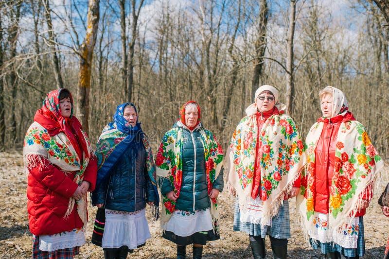 春天异教的节日  年长妇女跳舞并且唱歌,看见冬天并且见面春天在森林里 免版税库存图片