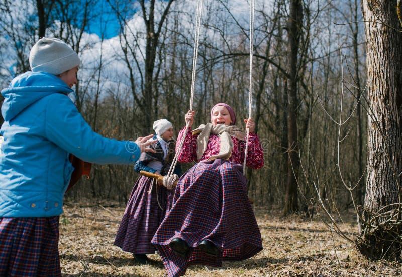 春天异教的节日  摇摆在高摇摆的孩子,以春天森林为背景 免版税库存图片