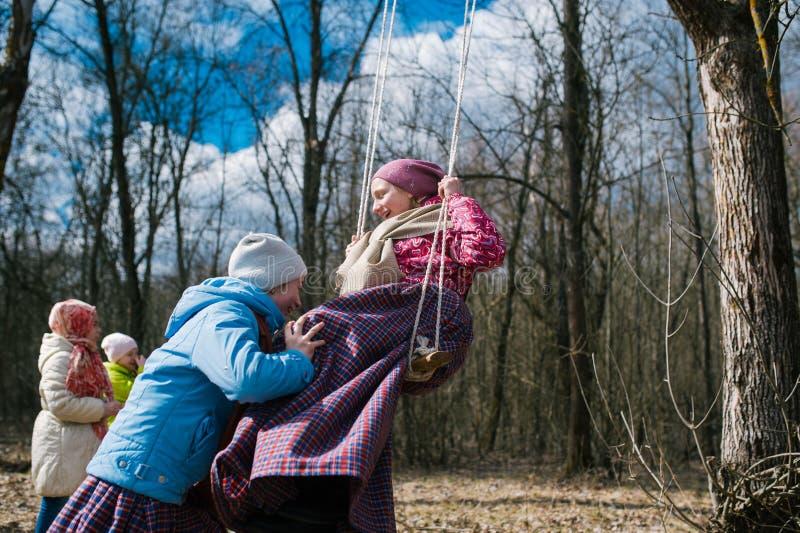 春天异教的节日  摇摆在高摇摆的孩子,以春天森林为背景 库存照片