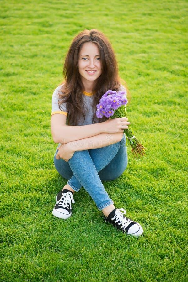 春天惊奇 妇女享用放松绿草背景 夫人享用嫩花花束 阴物和柔软 免版税库存照片