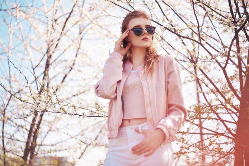 春天户外时尚在开花的树的女孩画象 花的秀丽浪漫妇女在太阳镜 肉欲的夫人 免版税库存照片