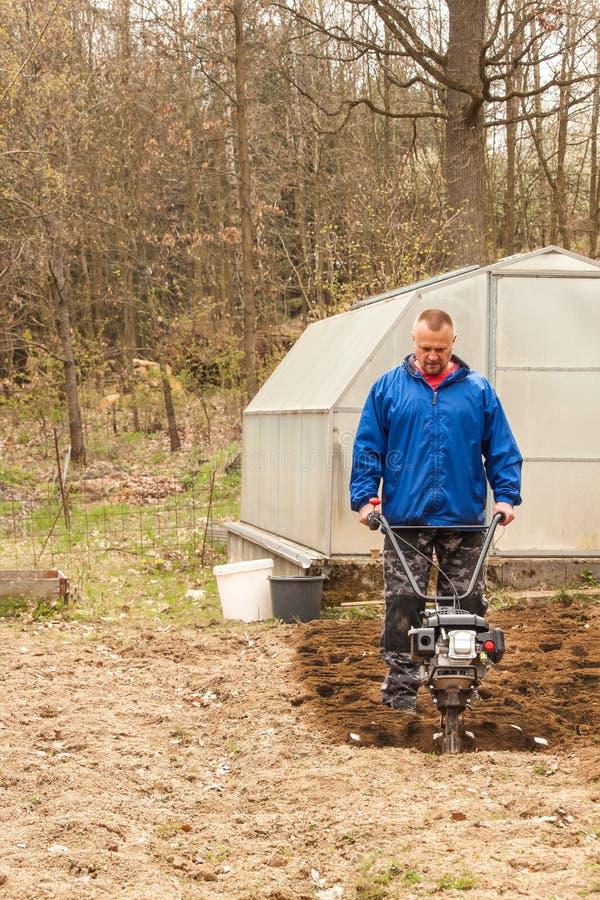 春天播种的准备土壤与翻土机 E 农夫犁有耕地机的土地,准备它 库存照片