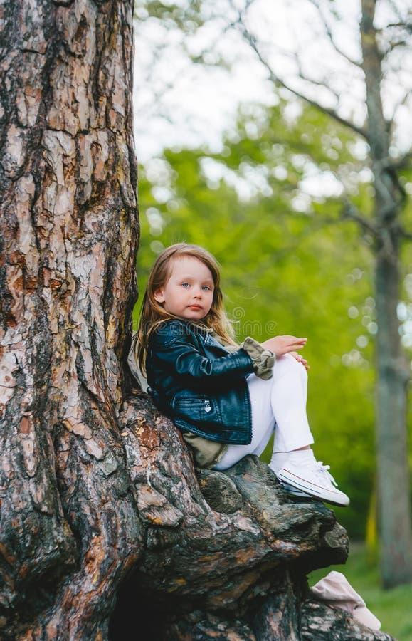 春天树干公园里,穿着皮夹克的小女孩在户外 免版税图库摄影
