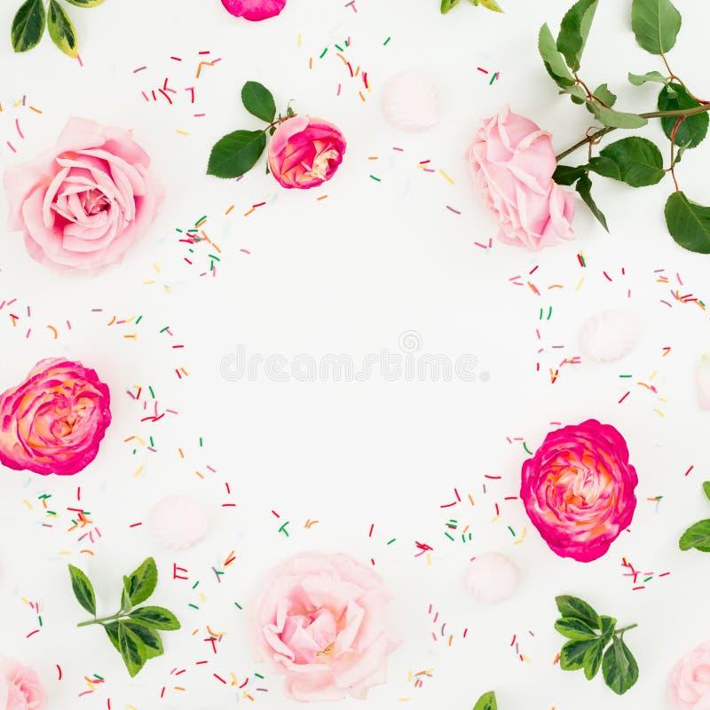 春天框架 粉红彩笔玫瑰花和糖果五彩纸屑的花卉构成在白色背景 平的位置,顶视图 库存照片