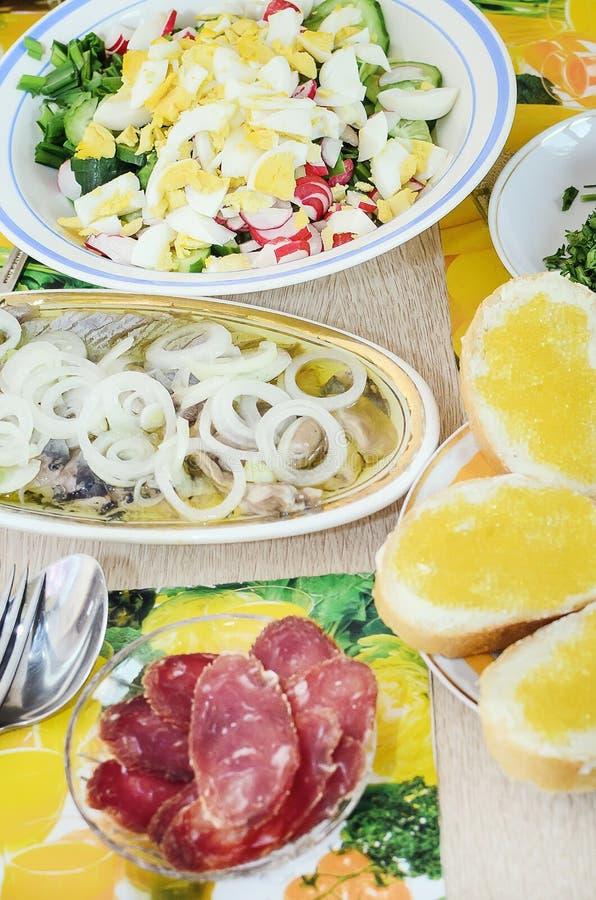 春天沙拉用鸡蛋、黄瓜和萝卜、鲱鱼用葱和切好的香肠立场在桌上 有用和鲜美午餐 免版税库存照片