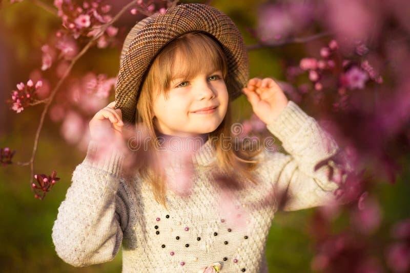 春天画象,帽子步行的可爱的女孩在开花日落的树庭院里 免版税库存图片
