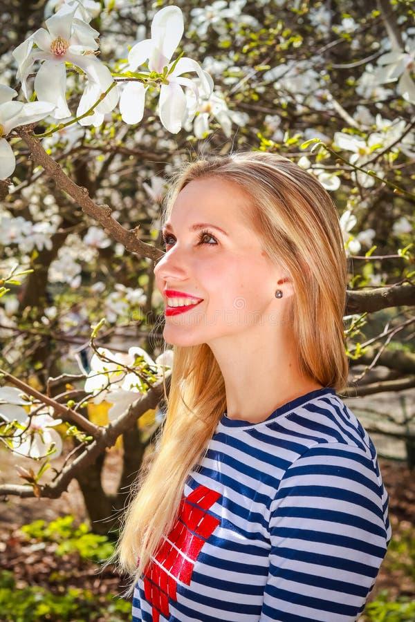 春天白肤金发的女孩画象站立在开花的庭院里的 免版税库存图片