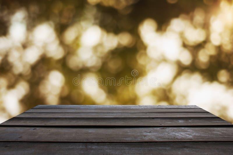 春天背景与一个黑木地板的光bokeh 库存照片