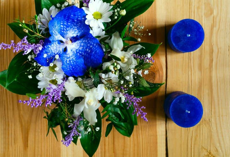 春天花和蓝色手工制造蜡烛花束在轻的木背景 免版税图库摄影