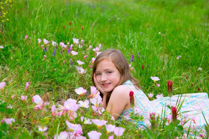 春天草甸的儿童逗人喜爱的女孩有鸦片的开花 免版税库存照片