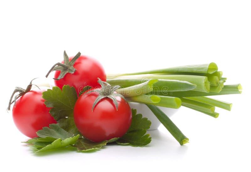春天葱和西红柿在碗 免版税库存照片