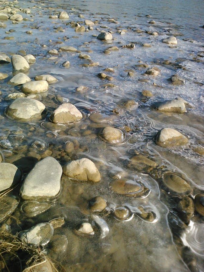 春天解冻,由河的岩石 免版税图库摄影