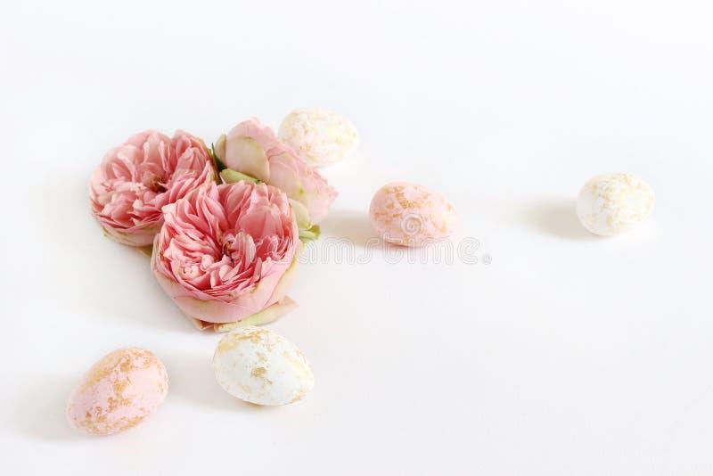 春天贺卡,邀请 与金黄说谎在白色桌上的斑点和玫瑰色花的桃红色和白色复活节彩蛋 免版税库存照片
