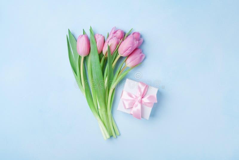 春天郁金香开花和在蓝色淡色台式视图的礼物盒 贺卡为生日、妇女或者母亲节 平的位置 免版税图库摄影