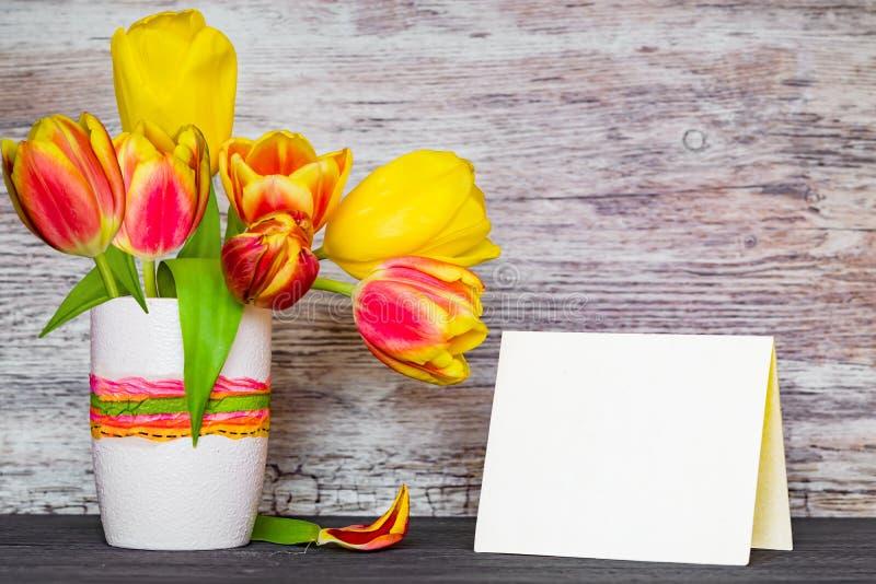 春天郁金香花束在塑料色的杯的在与老纸一张的一张木葡萄酒桌上,嘲笑, 免版税库存图片