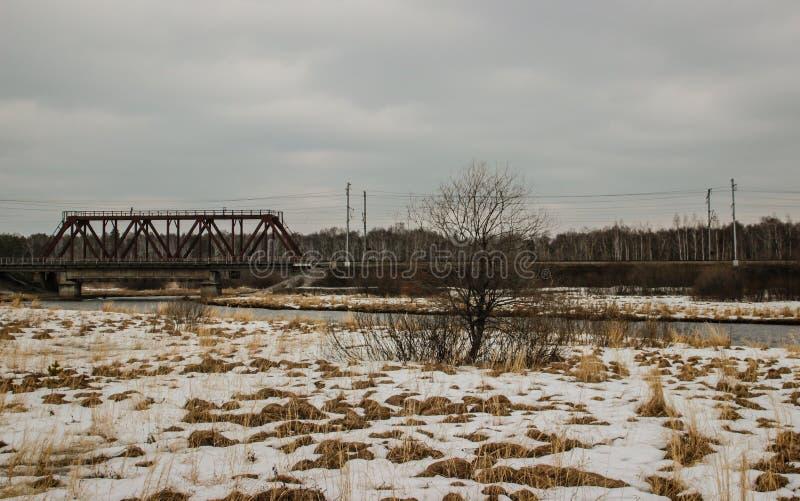 春天,在那里有些地方是雪,在河,村庄的铁路桥 免版税库存图片