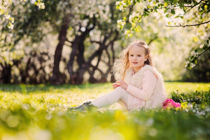 春天画象漂亮的孩子女孩走室外在开花的庭院里 免版税库存图片