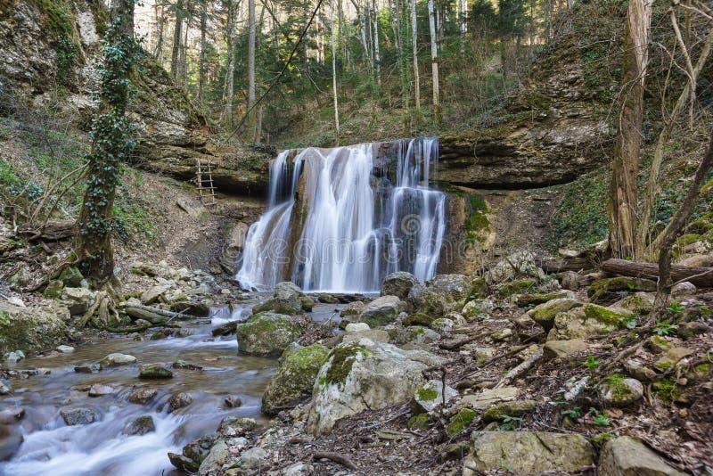 春天Kaverinsky大瀑布从石壁架流动下来在高加索山脉的树木繁茂的峡谷 高涨途径 免版税库存图片