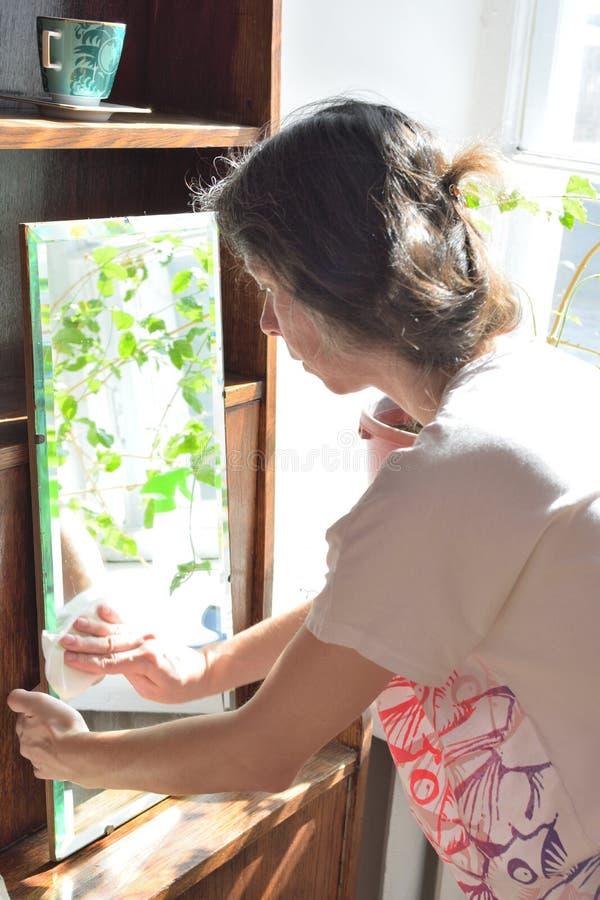 春季大扫除葡萄酒镜子的年轻俏丽的妇女 库存照片