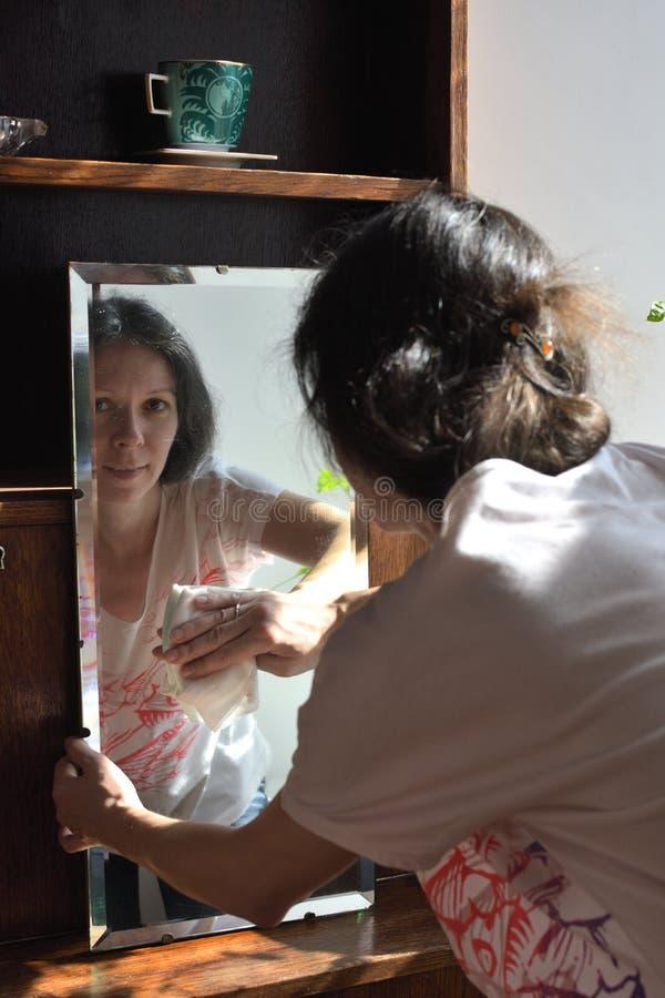 春季大扫除葡萄酒镜子的年轻俏丽的妇女 库存图片
