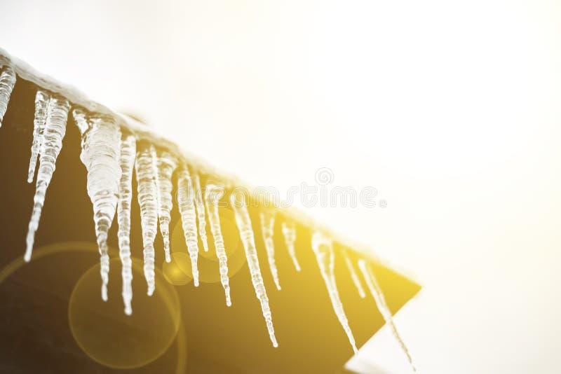 春季开始,晴朗的天空和冰柱从屋顶壁架和熔化的f垂悬 免版税图库摄影