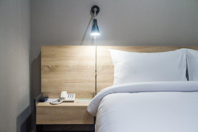 春武里市,泰国–2018年6月24日:在一张舒适的床上的白色枕头与舒适卧室 库存图片